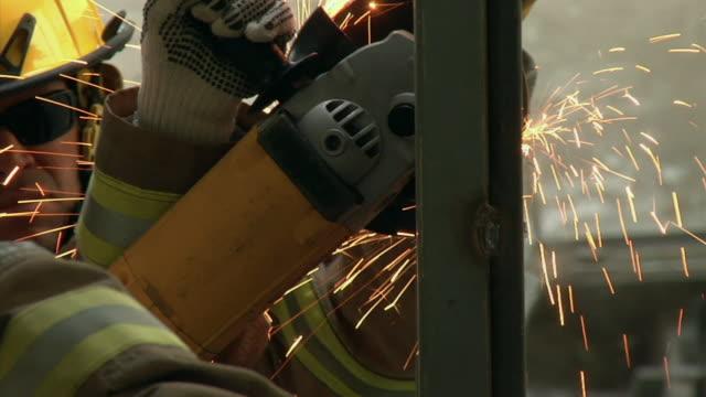 CU SELECTIVE FOCUS Fire fighters practicing sawing through steel, Ecuador