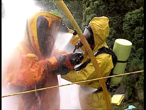 MCU Fire fighters washing away chemical residue from protective suits