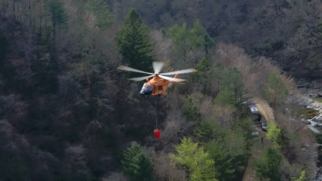 fire fighting helicopter flying for extinguishing forest fire at odaesan mountain / gangwon-do, south korea - turning stock videos & royalty-free footage