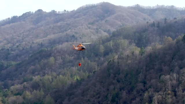 fire fighting helicopter flying for extinguishing forest fire at odaesan mountain / gangwon-do, south korea - asche stock-videos und b-roll-filmmaterial