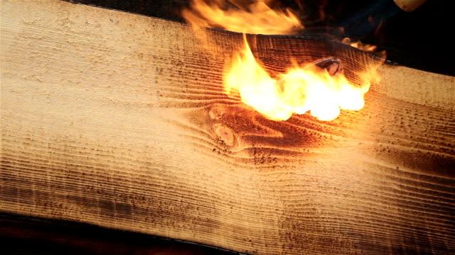 feuer flamme brennt eine holzoberfläche. - brennbar stock-videos und b-roll-filmmaterial