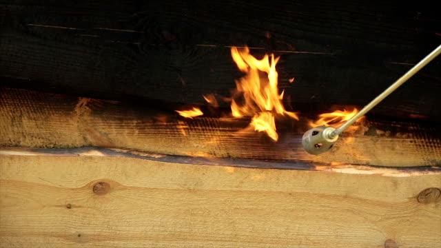 fire flame burns a wooden surface. - timber stock videos and b-roll footage
