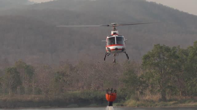 森林山の水槽と火のヘリコプター - 軍用機点の映像素材/bロール