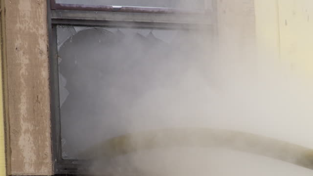 fire hose extending through a broken window into a smoke-filled interior; smoke billows and water shoots out - myrtle creek stock videos & royalty-free footage