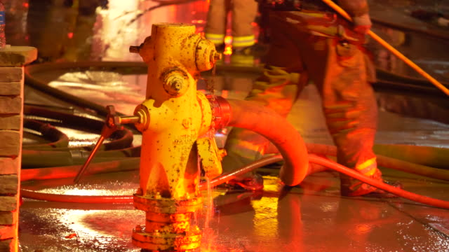fire hydrant and firemen fighting to put out a house fire at night in a neighborhood. - fire hydrant stock videos & royalty-free footage