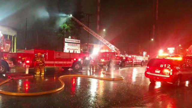 fire in an auto repair shop made firefighters take action with a rainy night in their favor. - ナイトイン点の映像素材/bロール