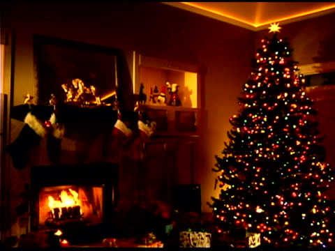 fire in fireplace in living room with christmas decorations - soggiorno video stock e b–roll
