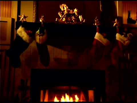 fire in fireplace in living room with christmas decorations - stockings stock videos & royalty-free footage