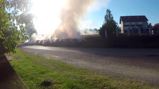 vídeos y material grabado en eventos de stock de fuego en el campo cerca de la ciudad - quemar