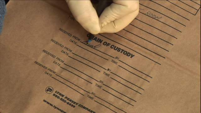a fire investigator labels an evidence bag. - arson stock videos & royalty-free footage