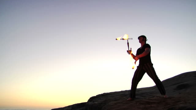fire juggling sunset - juggler stock videos and b-roll footage