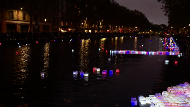 fire lanterns on a canal in paris in a tribute to the victims of the bataclan terrorist attacks one year on - memorial event stock videos & royalty-free footage