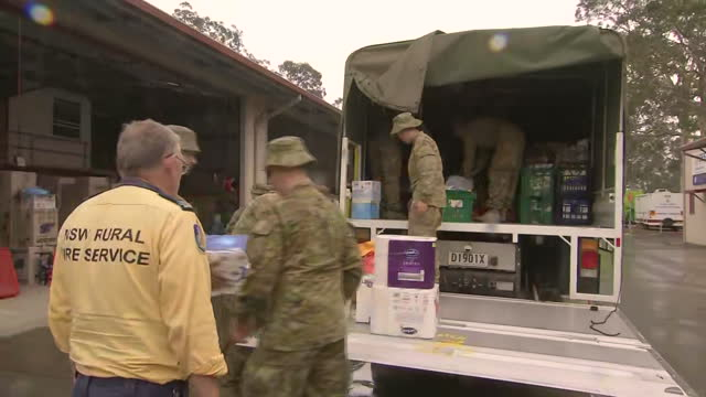 fire rescue workers load supplies onto a truck in australia. - environment or natural disaster or climate change or earthquake or hurricane or extreme weather or oil spill or volcano or tornado or flooding stock videos & royalty-free footage