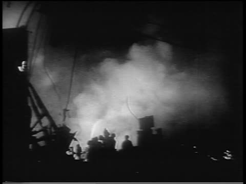 B/W 1938 fire scene with silhouette of people in foreground after hurricane at night / Northeast US / newsreel