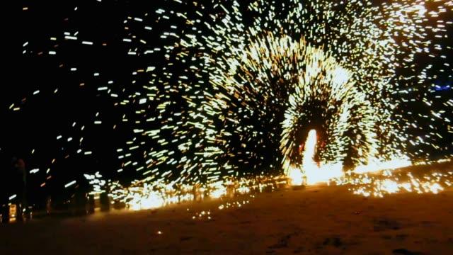 vídeos y material grabado en eventos de stock de lanzador de fuego en la playa por la noche - ir marcha atrás