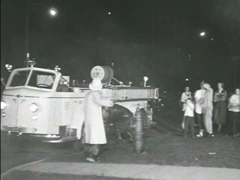 firefighters dramatization fire truck at hydrant tu smoking window firemen w/ hose others running bg firefighter climbing into smoking window - syracuse stock videos & royalty-free footage