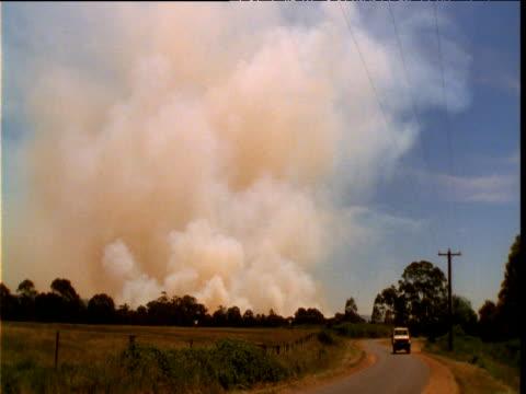 Fire truck drives past as smoke billows from bush fire, Queensland, Australia