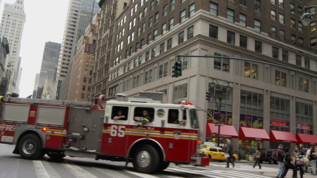 ms shaky fire truck driving on busy street / new york city, new york, usa - 消防車点の映像素材/bロール