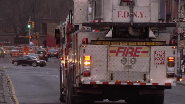 fdny fire truck going down a manhattan street - fire department of the city of new york stock-videos und b-roll-filmmaterial