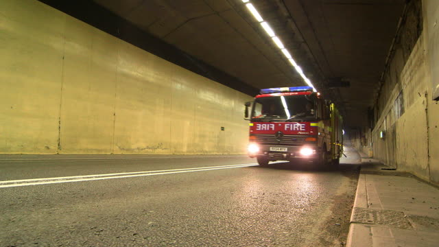 vídeos de stock e filmes b-roll de ws fire truck riding in tunnel / london, england, united kingdom - carro de bombeiro
