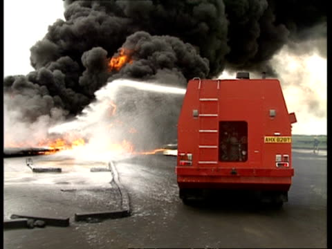 vídeos de stock e filmes b-roll de ms fire truck spraying fire with foam as it arrives at scene - carro de bombeiro