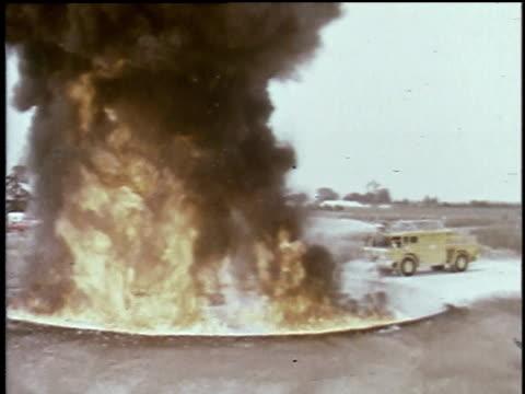 fire truck with sprayer approaching flames and black smoke on runway / foam truck / foam spraying / foamcovered fire fighter / firefighters on ground... - feuerwehr hinweisschild stock-videos und b-roll-filmmaterial