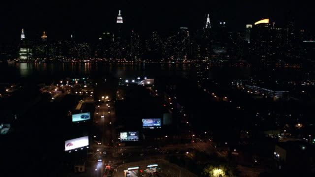 aerial, fire trucks driving on street, manhattan skyline illuminated at night in distance, new york city, new york, usa - underpass stock videos & royalty-free footage