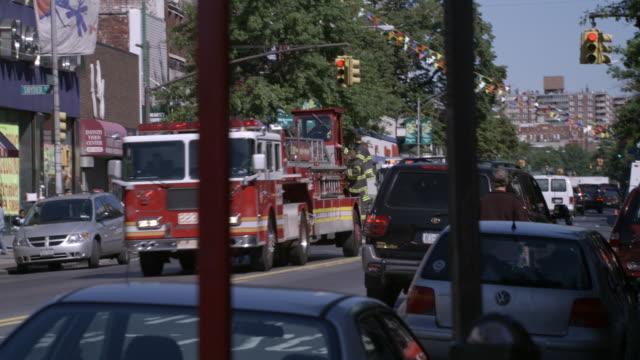 ms, pan, fire trucks driving on street, new york city, new york, usa - 消防車点の映像素材/bロール