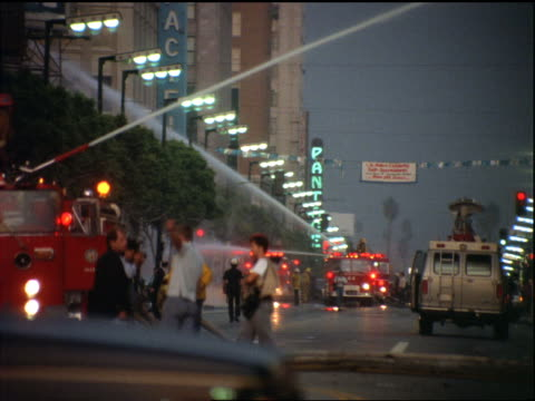 fire trucks + firefighters spraying hoses on city street at dusk / los angeles riots - 1992 stock videos & royalty-free footage
