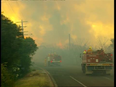 WA 2 Fire trucks on road next to bushfire