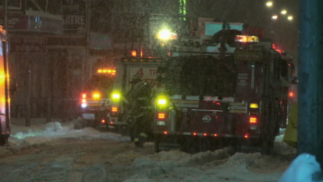 fire trucks parked with lights on in a snow storm. - fanghiglia video stock e b–roll