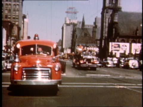 1951 montage fire trucks rushing along streets of detroit / michigan, united states - 消防車点の映像素材/bロール