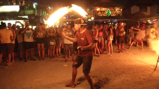 fire twirlers perform during the full moon party on the beach on ko phangan in thailand on jan 4 2015 a happy new year sign is lit up - ko phangan stock videos and b-roll footage