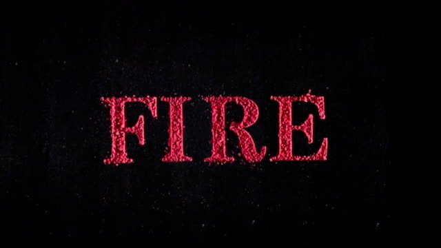 Fire written in red powder exploding in slow motion.