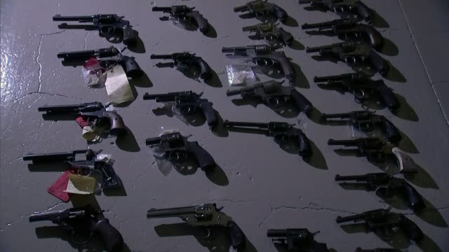 firearms dealer paul edmunds jailed for 30 years int various shots of antique guns in darkened room close shot of bullets bags of bullets on table top - table top shot stock videos & royalty-free footage