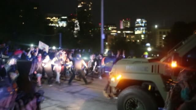 firecrackers were fired and a police hummer was ushered back by a large group of protesters who gathered in boston on tuesday to denounce police... - suv stock videos & royalty-free footage