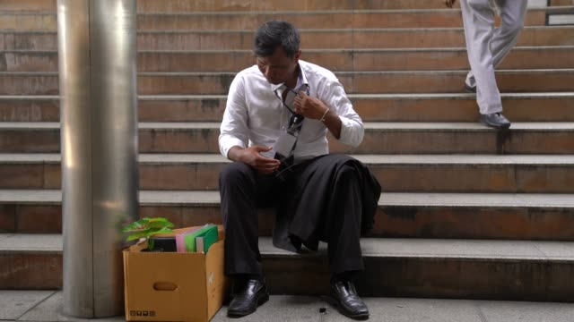 fired businessman feeling extremely tired while sitting down on the floor with his belongings box. - carrying stock videos & royalty-free footage