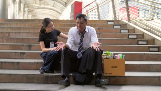stockvideo's en b-roll-footage met ontslagen zakenman gevoel extreem moe tijdens het lopen uit voor het kantoor. witte kraag werknemer wordt ontslagen haar zittend op de stoep te bedelen een nieuwe baan. - verdwaald