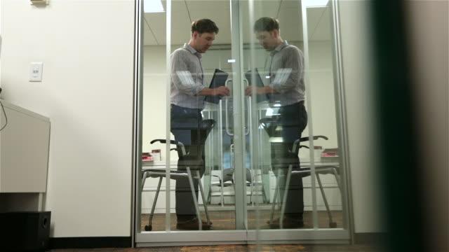 fired employee leaves boss' office in disbelief, walks away down office hallway - türrahmen stock-videos und b-roll-filmmaterial