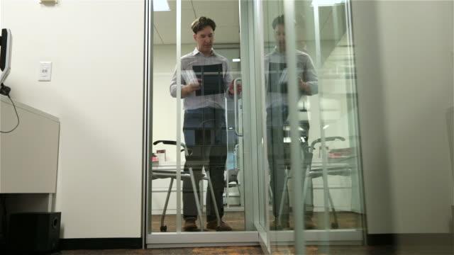 Fired employee leaves boss' office in disbelief, walks down office hallway toward camera