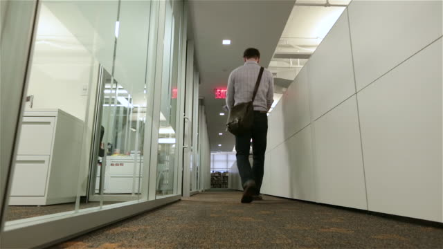 fired employee walks despondently away down office hallway with box of belongings - exit sign stock videos & royalty-free footage