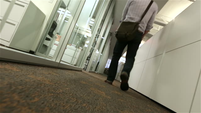 fired employee walks despondently away down office hallway with box of belongings (dutch, dolly shot) - korridor stock-videos und b-roll-filmmaterial