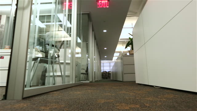fired employee walks despondently down office hallway toward camera with box of belongings (dolly shot) - loss stock videos & royalty-free footage