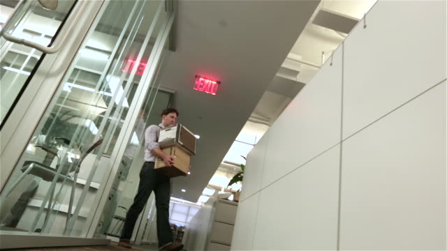vidéos et rushes de fired employee walks despondently down office hallway toward camera with box of belongings (dutch, dolly shot) - chômage