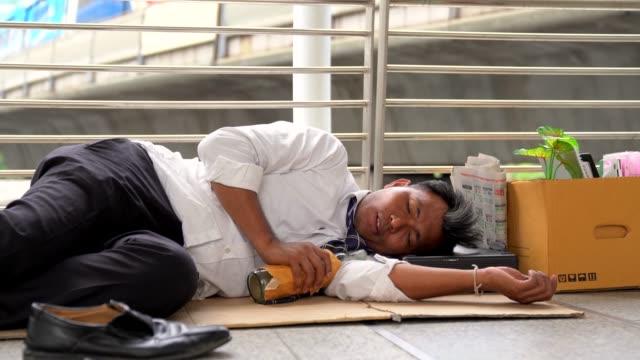 路上で助けを乞うために床に横たわっている仕事を懇願する解雇されたサラリーマンの男性。経済危機、経済改革の概念。ホワイトカラーの従業員は、彼女が新しい仕事を物乞いするために� - white collar worker点の映像素材/bロール