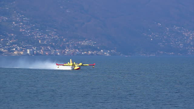 firefighter aircraft filling tanks on a lake - propeller stock videos & royalty-free footage