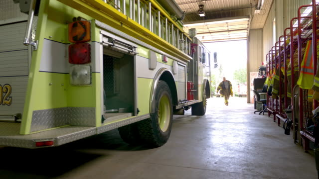 vidéos et rushes de a firefighter carries and stores equipment on the fire truck at the station - vigilance