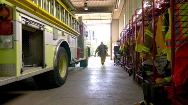 a firefighter carries and stores equipment on the fire truck at the station - firefighter stock videos and b-roll footage