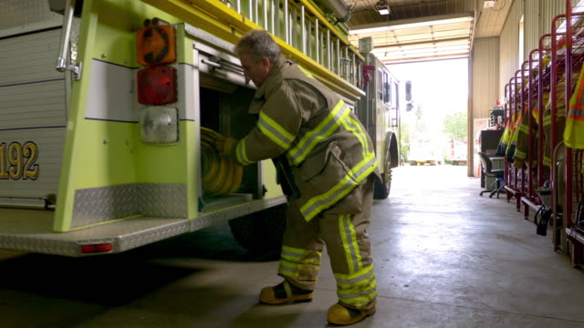 firefighter carrying hose walking away from camera. - fire station stock videos & royalty-free footage
