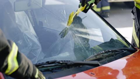 vidéos et rushes de slo mo pompier coupe le pare-brise d'une voiture - trois personnes